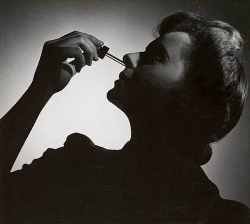 An image of Untitled (woman with nose dropper) by Max Dupain