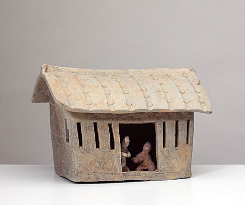 An image of Model of a house [with two kneeling figures inside the house]