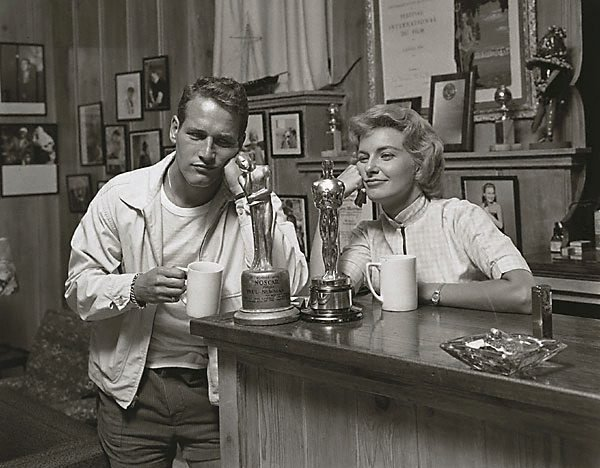 "An image of Paul Newman and Joanne Woodward ""admiring"" their awards. His: 'Noscar' for not having received an Oscar (yet) and Hers; for ""The Three Faces of Eve"". Photo taken for the Saturday Evening Post in 1958"