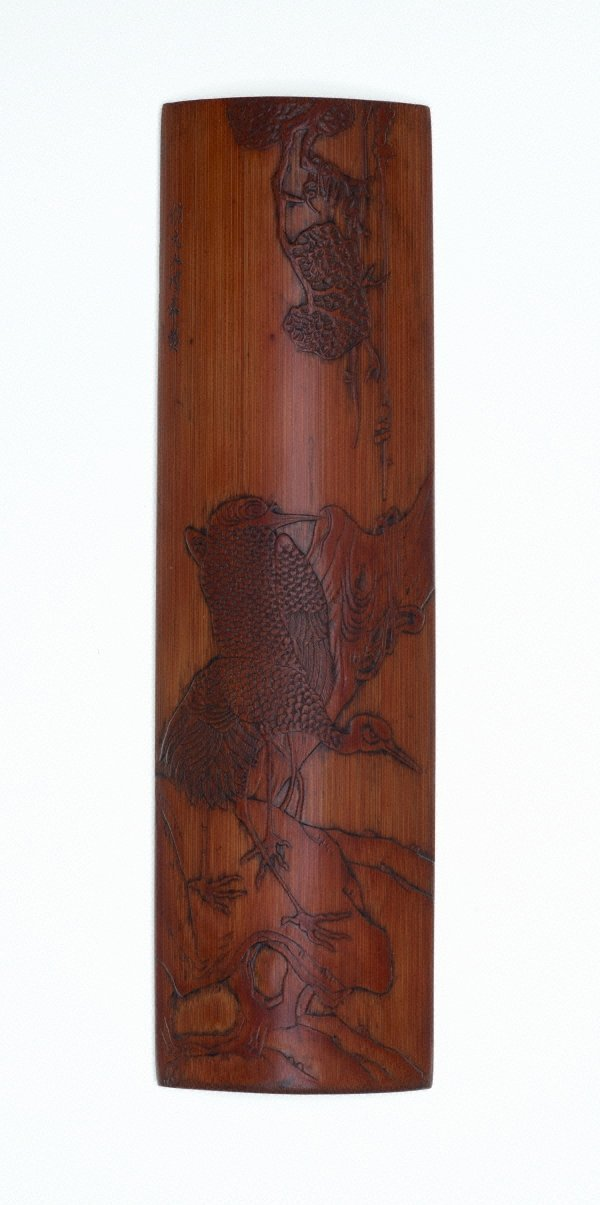 An image of Bamboo wrist-rest carved with two cranes on rocks under a tree in low relief
