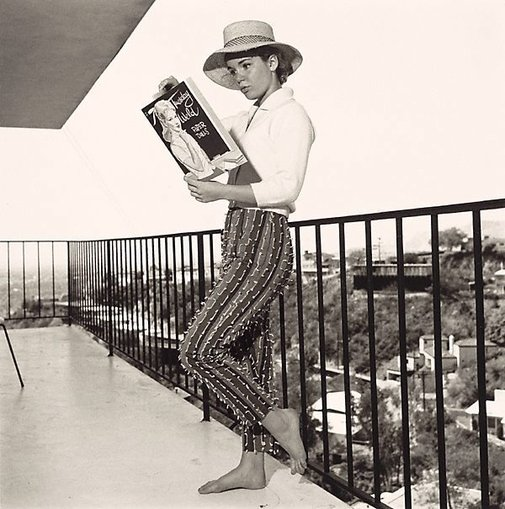 An image of Tuesday Weld looking at a Tuesday Weld Cut Out Doll Book on the balcony of her Los Angeles Home by Sid Avery
