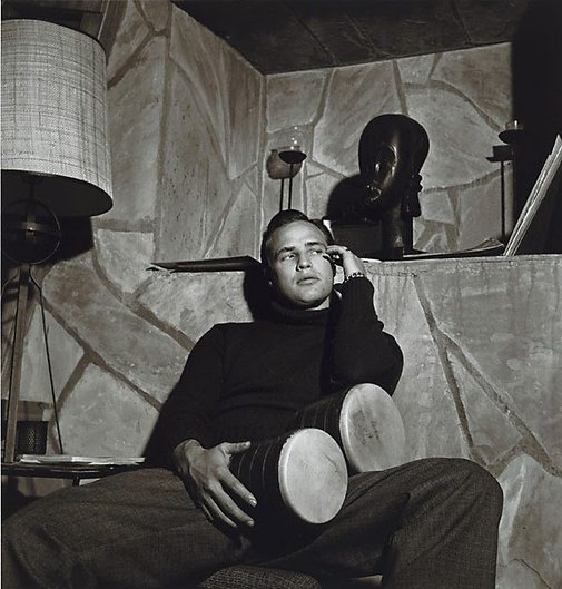 An image of Marlon Brando with bongo, and African mask by Sid Avery