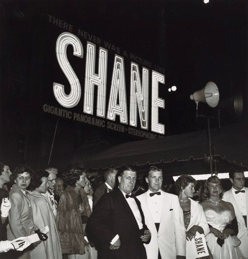 "An image of Director, George Stevens with his son, George Jr at the Hollywood premiere of his movie ""Shane"" by Sid Avery"