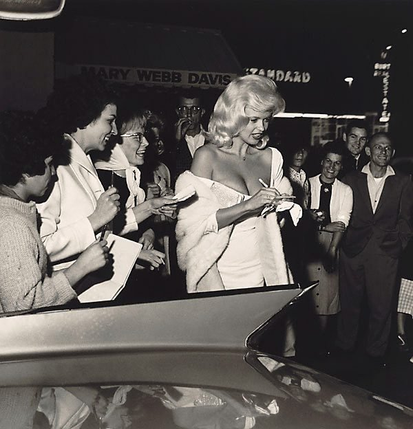 An image of Jayne Mansfield signing autographs in front of Dino's restaurant on the Sunset Strip in Los Angeles. Photographed in 1961