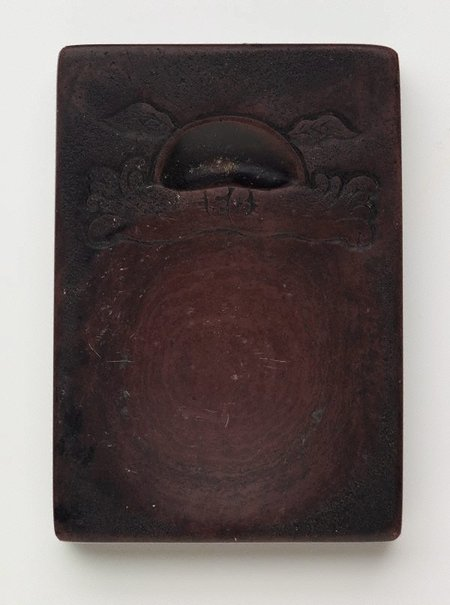 An image of Ink stone with decoration on the surface and inscriptions on the side by