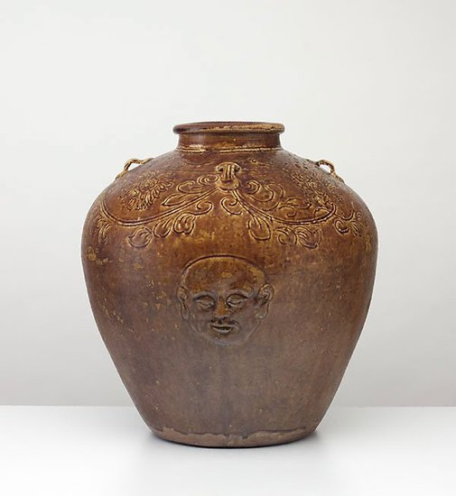 An image of Globular jar decorated with relief 'head and hand' motif by
