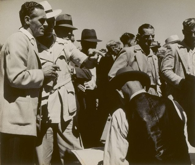 An image of 12 men at the races