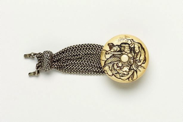 An image of 'Manju' netsuke of woodcutter and woman, with multiple silver chains [which originally would have attached it to a tobacco pouch]