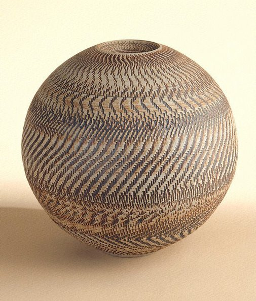 An image of Round unglazed pot with iron oxide colouring and chattered decoration by SHIGA Shigeo