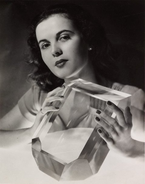 An image of June Prior photographed with a perspex scaled model of a perfect sugar crystal by John Lee Studio