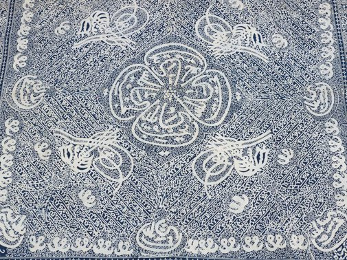 An image of Batik head cloth with stylised Islamic calligraphy design by