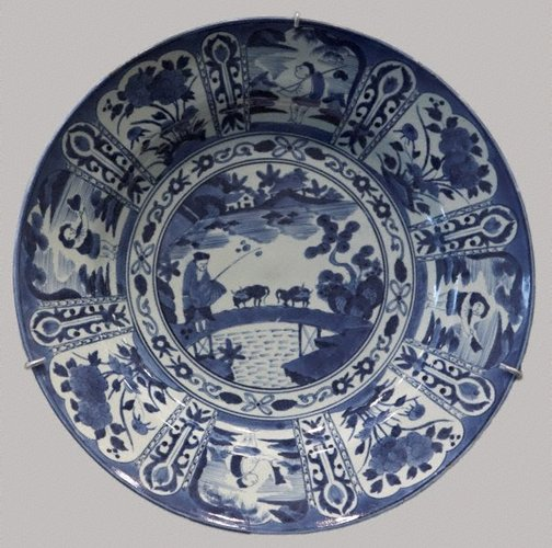 An image of Large charger with design of landscape with fisherman in the centre and alternating figure and flower patterns around it by Arita ware