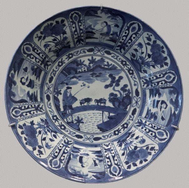 An image of Large charger with design of landscape with fisherman in the centre and alternating figure and flower patterns around it