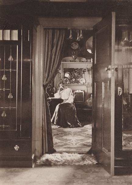 An image of Untitled (early interior with seated woman) by Harold Cazneaux