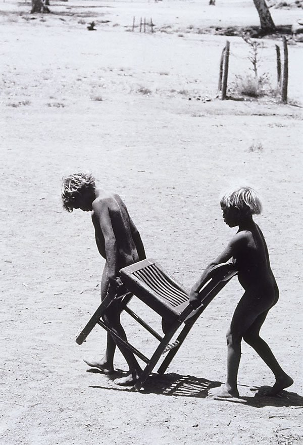 An image of Pitjantjatjara children with chair, South Australia