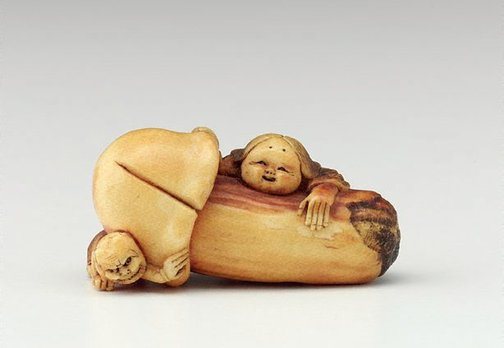 An image of Netsuke in the form of a mushroom with 'okame' leaning against it and 'oni' crouching under it by