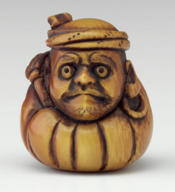 An image of Netsuke in the form of Daruma with a fly whisk, wearing a towel round his head