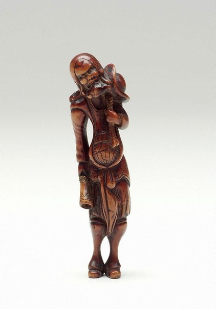 An image of Netsuke in the form of a Dutchman with a hat, holding a horn by
