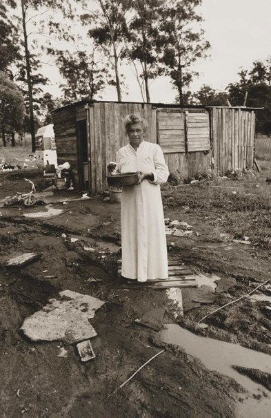 An image of Woman standing near electric power cord in water, Burnt Bridge by Mervyn Bishop