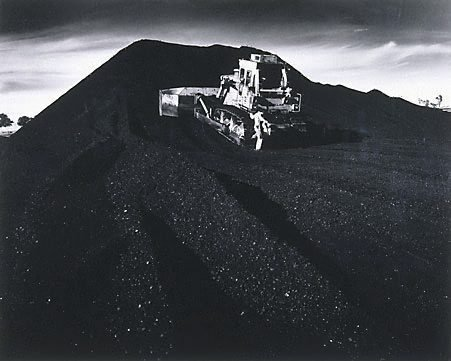 An image of A tractor pushing coal at Mt. Thorley rail terminal by Max Dupain