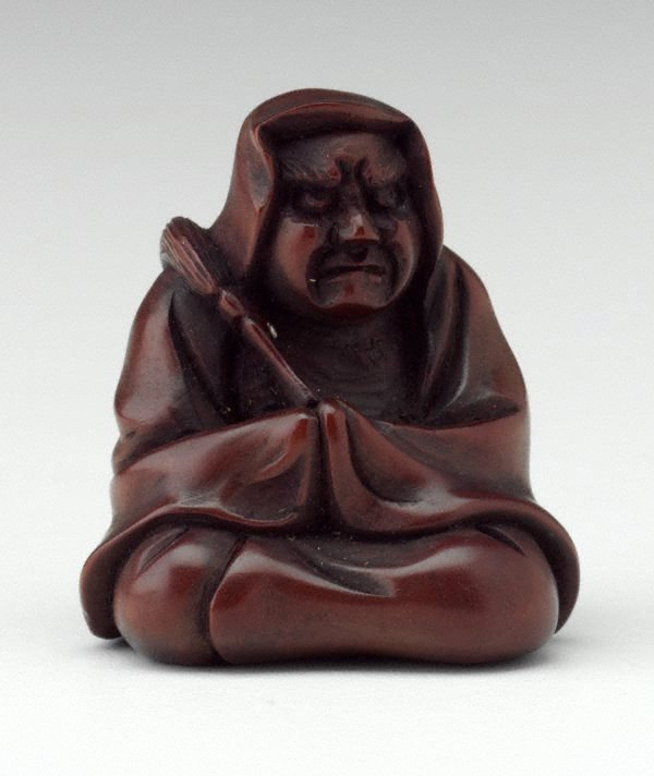 An image of Netsuke in the form of a seated Daruma, holding a fly whisk