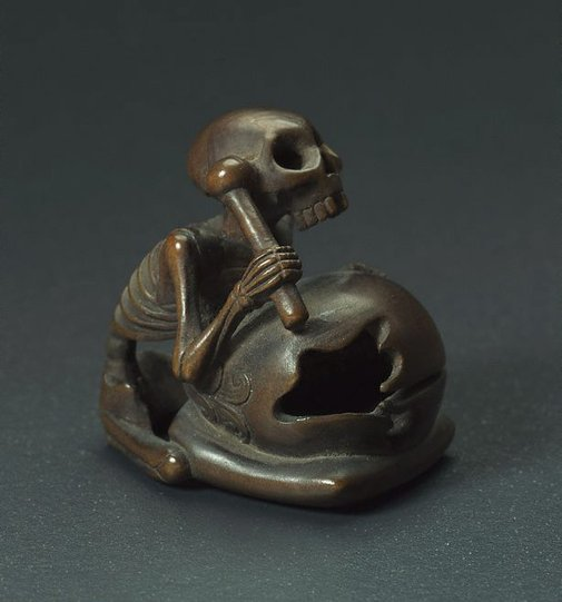 An image of Netsuke in the form of a seated skeleton hitting a 'wooden fish' bell ('mokugyo') by