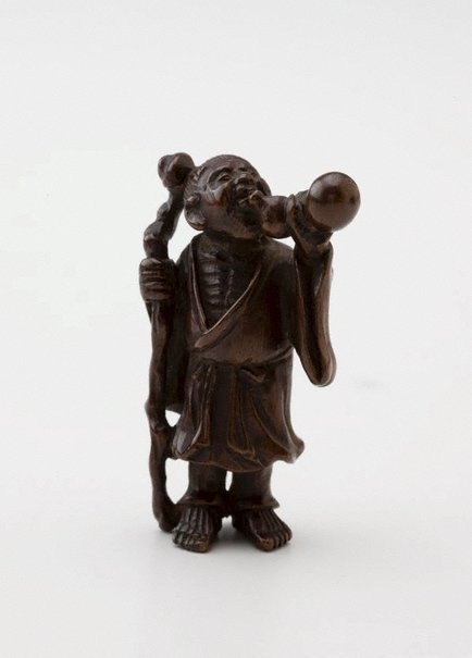 An image of Netsuke in the form of Chôkarô 'sennin' with a staff, drinking from a gourd by