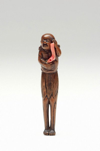 An image of Netsuke in the form of an old South Sea Islander holding red coral by