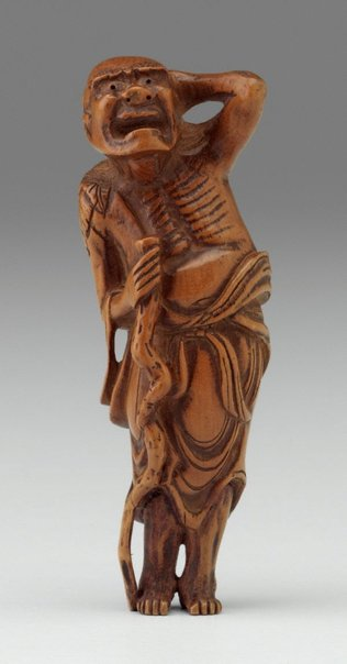 An image of Netsuke in the form of a 'sennin' (mountain recluse) holding his hair and a staff by