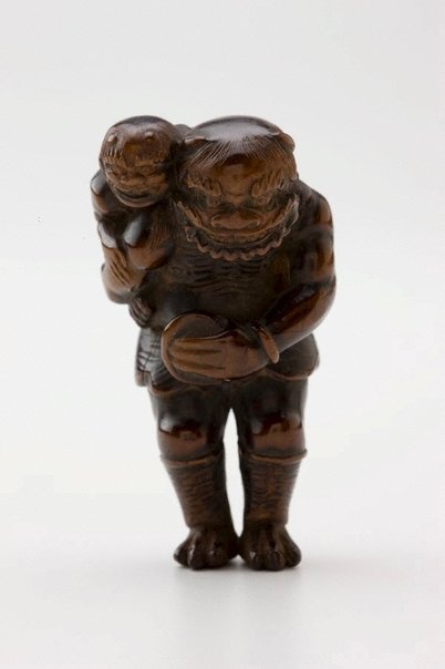 An image of Netsuke in the form of 'oni' carrying a child on his back, and a bowl in front by