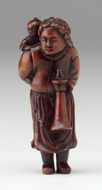 An image of Netsuke in the form of a curly-haired Dutchman carrying a child on his back, holding a horn by