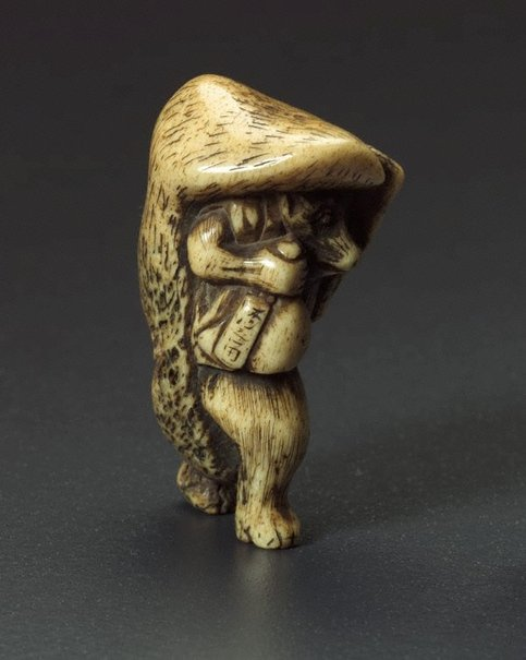 An image of Netsuke in the form of a badger carrying a 'sake' bottle by