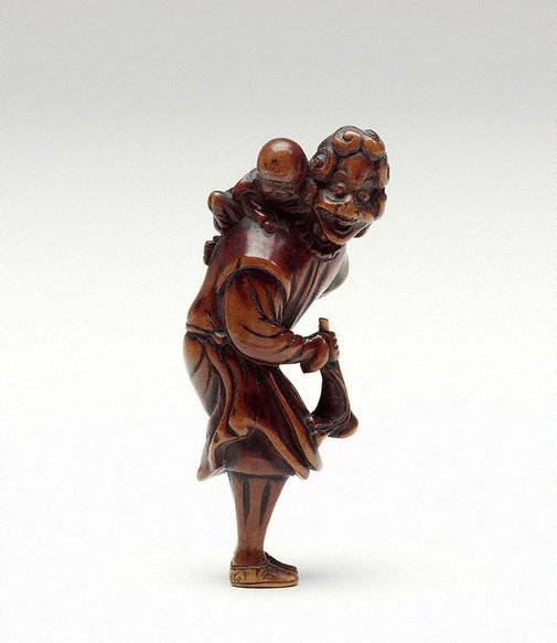 An image of Netsuke in the form of a foreigner with a coat, carrying a child and a horn by