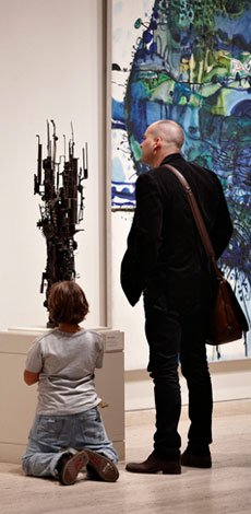 Adult and child visitor looking at a Klippel sculpture and Olsen painting
